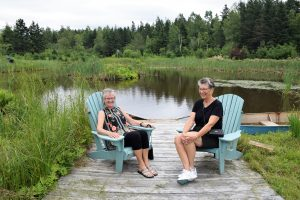 Victorian Garden Party A Success - women sitting on chairs in front of a lake